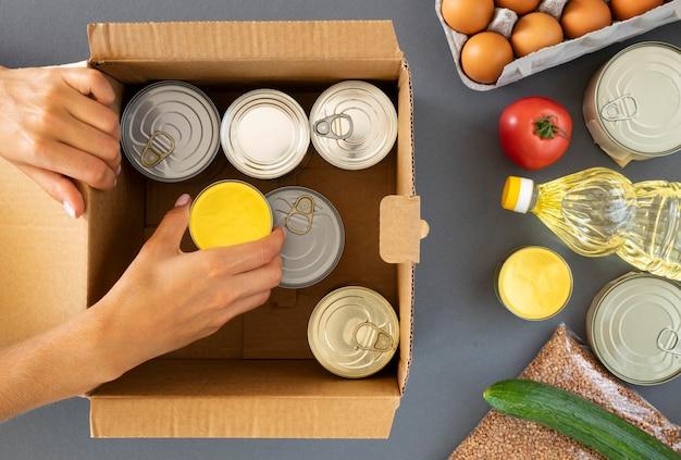 Vista superior da mão preparando doações de alimentos