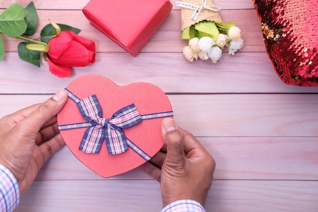 Vista superior da mão segurando a caixa de presente em forma de coração