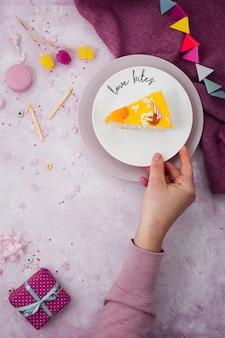 Vista superior da mão segurando a fatia de bolo com presente