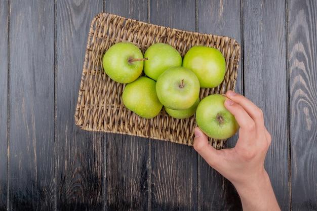 Vista superior da mão segurando a maçã e maçãs verdes no prato de cesta na mesa de madeira