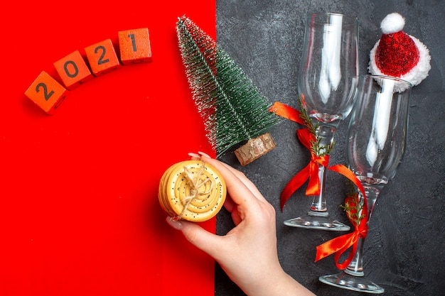 Vista superior da mão segurando biscoitos empilhados, números da árvore de natal, chapéu de papai noel em fundo vermelho e preto