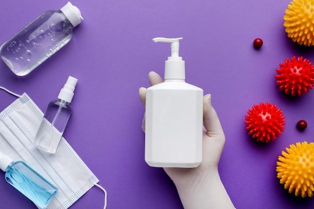 Vista superior da mão segurando o dispensador de sabão líquido com vírus