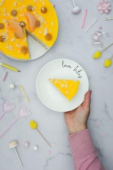Vista superior da mão segurando o prato com uma fatia de bolo
