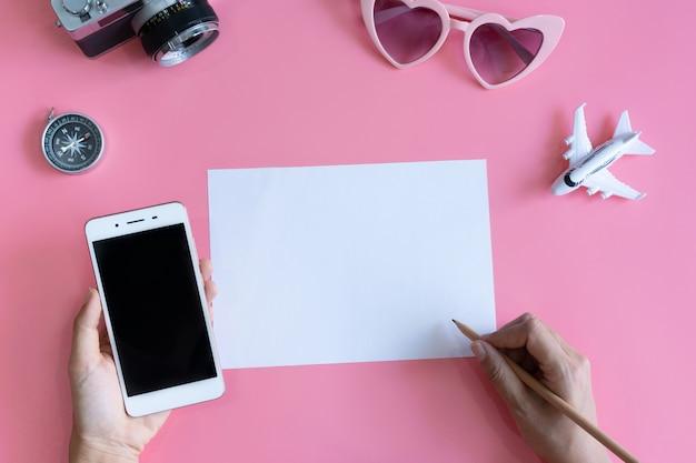 Vista superior da mão segurando o telefone celular enquanto escrevia em papel branco, acessórios de viagem, conceito de viagens. configuração plana, cópia espaço
