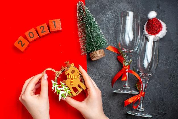 Vista superior da mão segurando os acessórios de decoração taças de vidro números da árvore de natal, chapéu de papai noel em fundo vermelho e preto