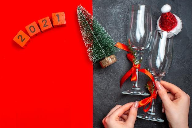 Vista superior da mão segurando taças de vidro, números da árvore de natal, chapéu de papai noel em fundo vermelho e preto