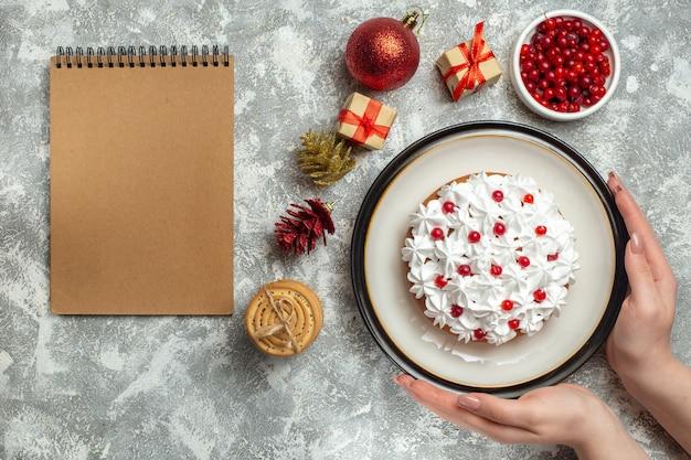 Vista superior da mão segurando um bolo delicioso com creme de groselha em um prato