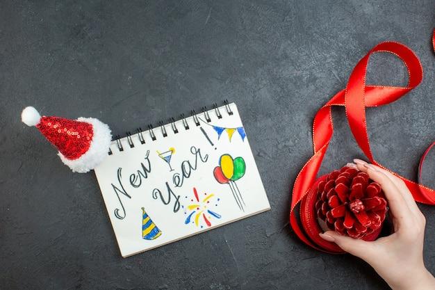 Vista superior da mão segurando um cone de conífera com fita vermelha e caderno com a escrita de ano novo e chapéu de papai noel em fundo escuro