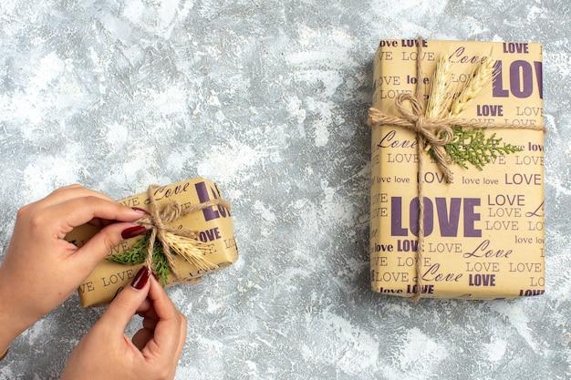Vista superior da mão segurando um dos lindos presentes embalados de natal com a inscrição de amor na superfície do gelo