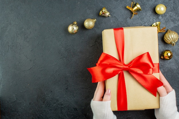 Vista superior da mão segurando uma caixa de presente com fita vermelha e acessórios de decoração em fundo escuro