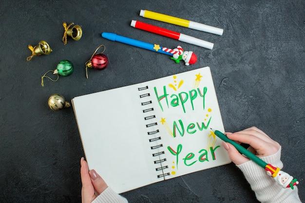 Vista superior da mão segurando uma caneta no caderno espiral com acessórios de decoração de escrita de feliz ano novo em fundo preto
