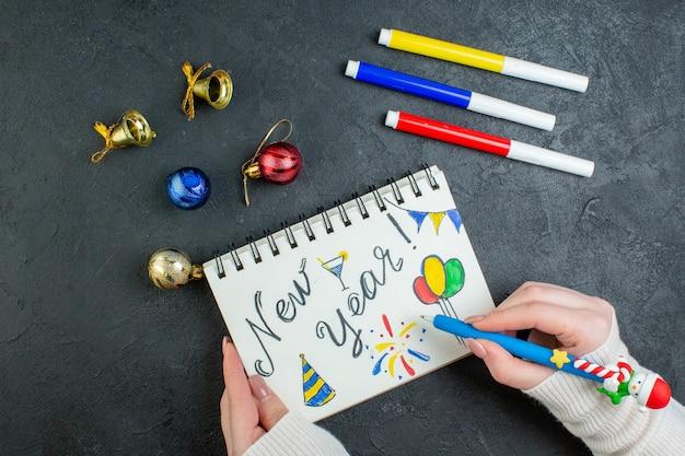 Vista superior da mão segurando uma caneta no caderno espiral com acessórios de decoração e escrita de ano novo em fundo preto