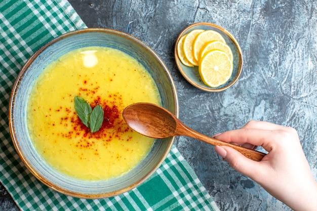 Vista superior da mão segurando uma colher e uma panela azul com uma saborosa sopa servida com hortelã e pimenta