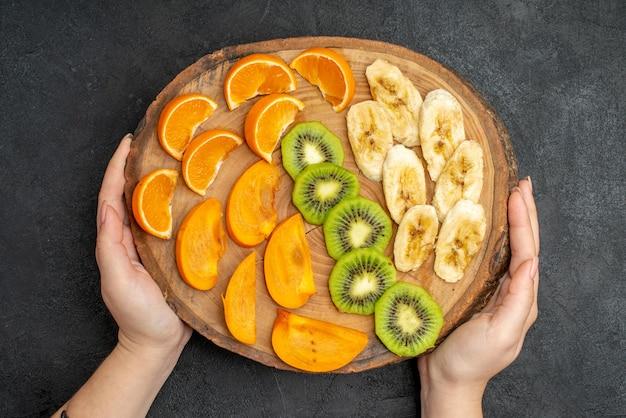 Vista superior da mão segurando uma fruta fresca orgânica natural definida em uma tábua na superfície escura