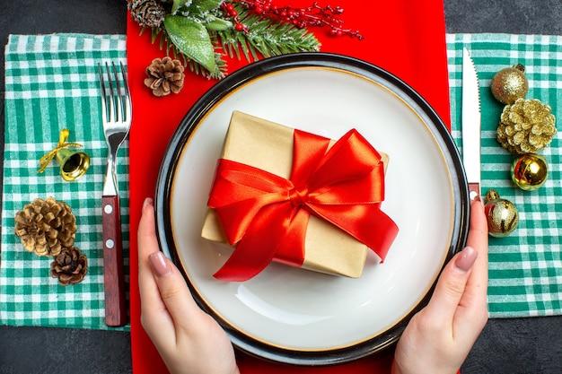 Vista superior da mão segurando uma linda caixa de presente com fita vermelha em forma de arco em um prato e acessórios de decoração de conjunto de talheres em toalha verde listrada