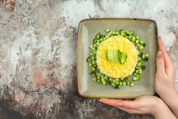 Vista superior da mão segurando uma saborosa salada servida com pepino picado no lado esquerdo em um fundo de cor mista