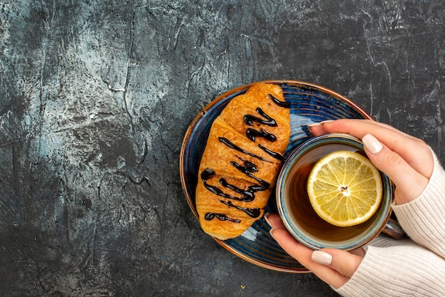 Vista superior da mão segurando uma xícara de chá preto delicioso croisasant no lado esquerdo na mesa escura