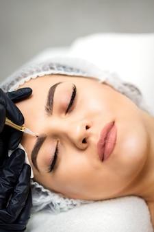 Vista superior da maquiagem definitiva nas sobrancelhas de uma jovem mulher caucasiana por meio de uma ferramenta especial de tatuagem