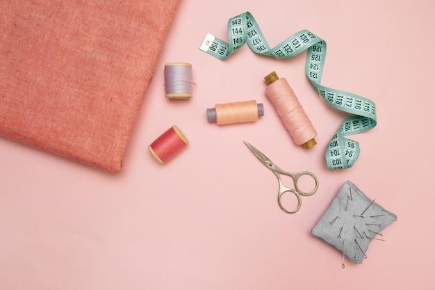 Vista superior da máquina de costura com acessórios para costura, tesoura e uma fita métrica em fundo rosa. posição vertical