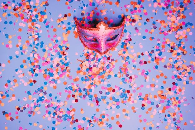 Vista superior da máscara de carnaval bonita com confetes coloridos sobre fundo azul