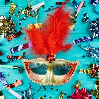 Vista superior da máscara de carnaval veneziano com penas em ouro e vermelho com material de decoração de festa