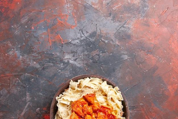 Vista superior da massa cozida com fatias de frango e molho na superfície escura da massa de massa escura