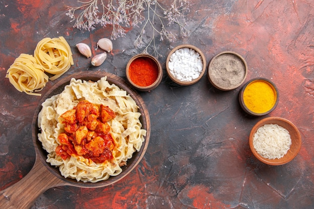 Vista superior da massa cozida com frango e molho em um prato escuro de massa escura de mesa