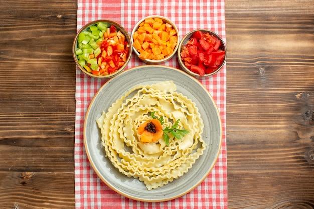 Vista superior da massa crua com vegetais fatiados no produto de ingrediente alimentar de refeição de vegetais de mesa marrom Foto gratuita