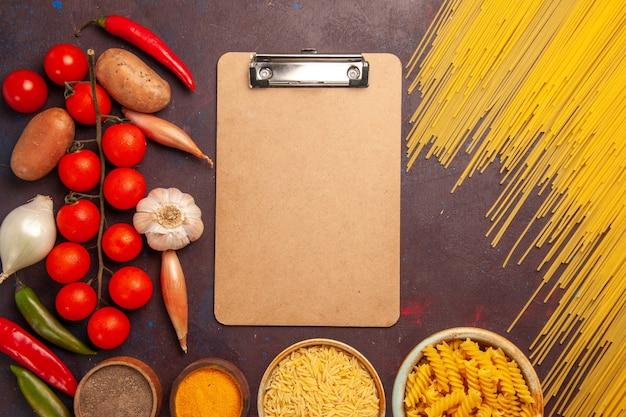 Vista superior da massa crua italiana com vegetais frescos e temperos em fundo escuro refeição de massa comida crua cor vegetal