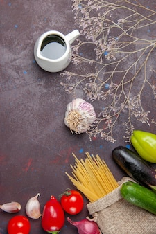 Vista superior da massa fresca crua com legumes na superfície escura, salada saudável, comida vegetal