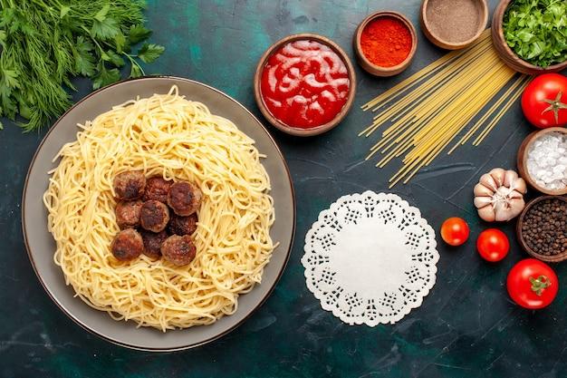 Vista superior da massa italiana cozida com almôndegas e temperos diferentes na superfície azul escura