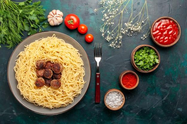 Vista superior da massa italiana cozida com almôndegas, temperos e verduras na superfície azul escura
