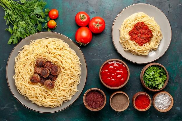 Vista superior da massa italiana cozida com carne e temperos na superfície azul escura