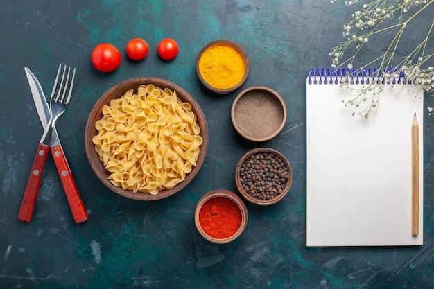 Vista superior da massa italiana crua com bloco de notas e temperos em fundo azul escuro ingrediente comida crua