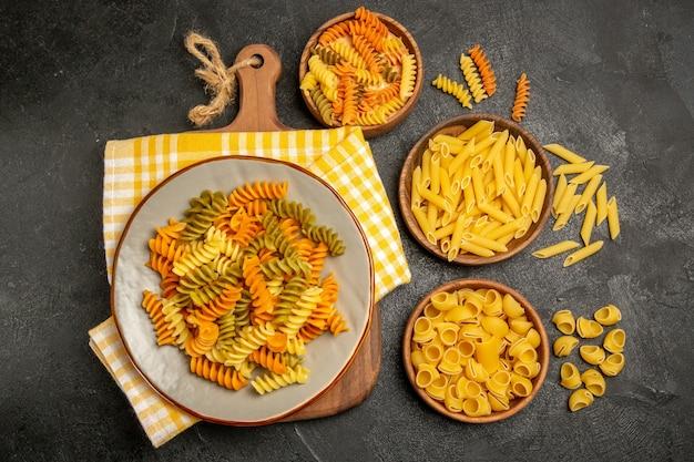 Vista superior da massa italiana crua com diferentes formas dentro dos pratos na cor cinza