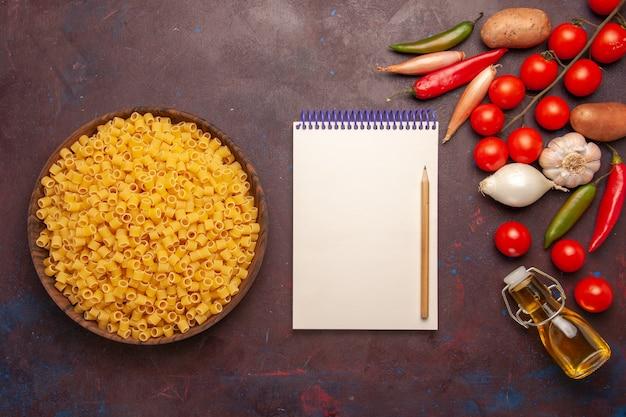 Vista superior da massa italiana crua com legumes frescos em comida de refeição de massa vegetal de fundo escuro
