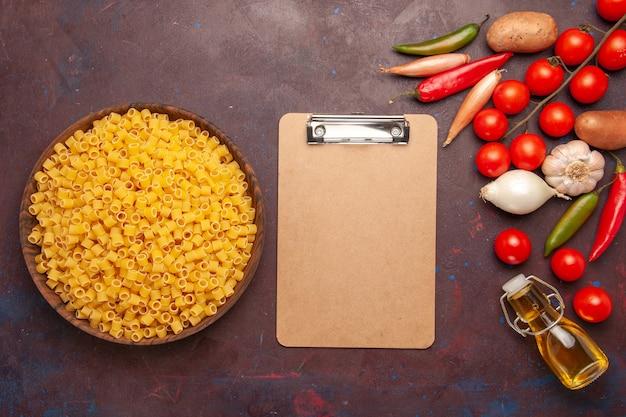 Vista superior da massa italiana crua com legumes frescos em fundo escuro refeição de massa de legumes cor de alimento