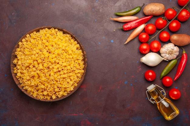 Vista superior da massa italiana crua com vegetais frescos no fundo escuro refeição de massa vegetal corante alimentar
