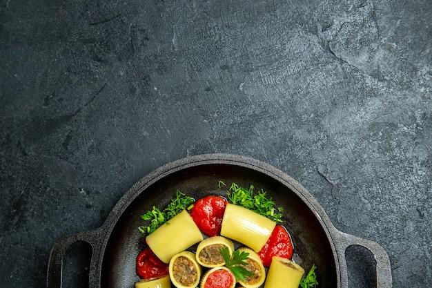 Vista superior da massa italiana crua com verduras de carne e molho de tomate dentro de uma panela em um fundo escuro