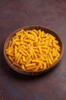 Vista superior da massa italiana crua dentro da bandeja de madeira na mesa escura.