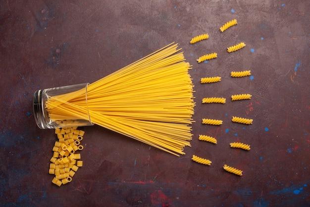 Vista superior da massa italiana crua formada há muito tempo de cor amarela sobre fundo roxo-escuro