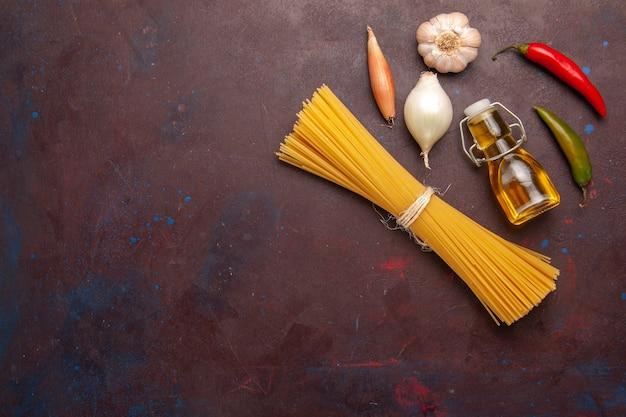 Vista superior da massa italiana crua formada há muito tempo em um fundo roxo-escuro refeição massa alimentícia