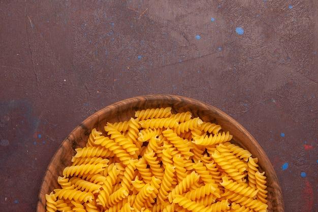 Vista superior da massa italiana crua pouco formada dentro do prato na mesa escura