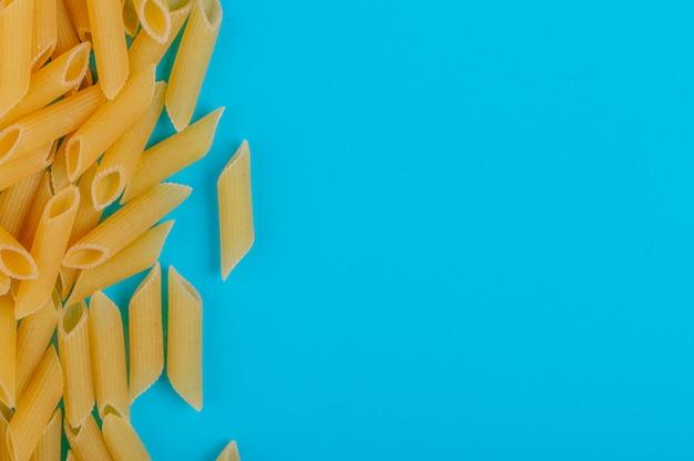 Vista superior da massa penne no lado esquerdo e superfície azul com espaço de cópia