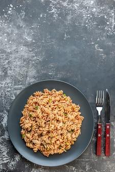 Vista superior da massa rotini em prato redondo, garfo e faca em mesa escura com lugar livre
