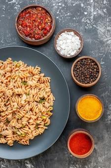 Vista superior da massa rotini em prato redondo, molho de tomate, especiarias diferentes em pequenas tigelas na mesa escura