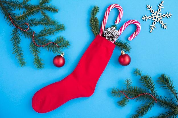 Vista superior da meia vermelha de natal com presentes no fundo azul. fechar-se.