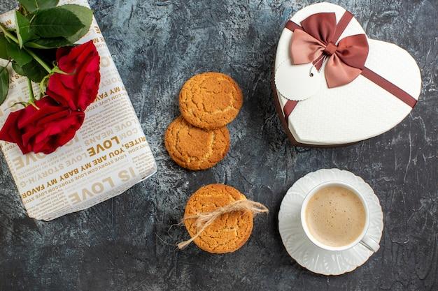 Vista superior da melhor surpresa com lindas caixas de presente e uma xícara de biscoitos de café rosas vermelhas para a pessoa amada em uma superfície escura e gelada