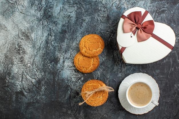 Vista superior da melhor surpresa com uma linda caixa de presente e uma xícara de biscoitos de café para a pessoa amada em uma superfície escura e gelada