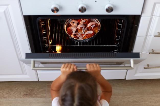 Vista superior da menina abrindo o forno, olhando para o saboroso croissant ou outro cozimento no forno, processo de cozimento na cozinha, pequena criança do sexo feminino de cabelos escuros quer doces deliciosos.